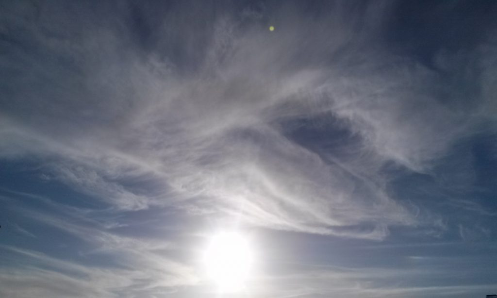 Sun and wispy clouds