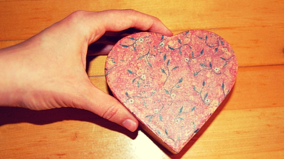 Hand holding a heart box.