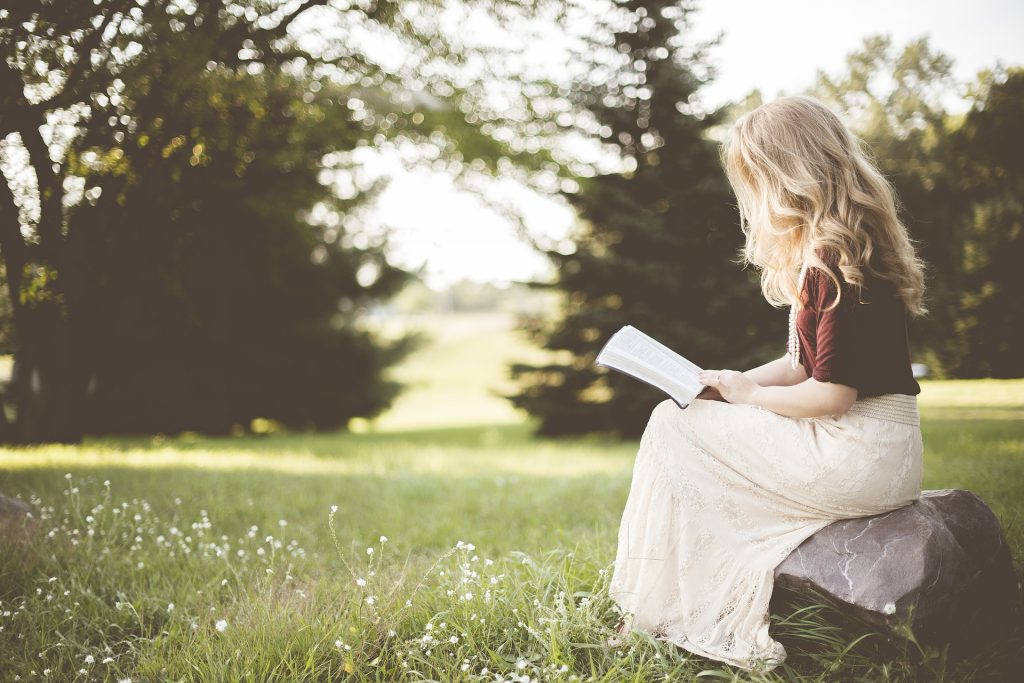 Woman reading book in meadow source: Pixabay
