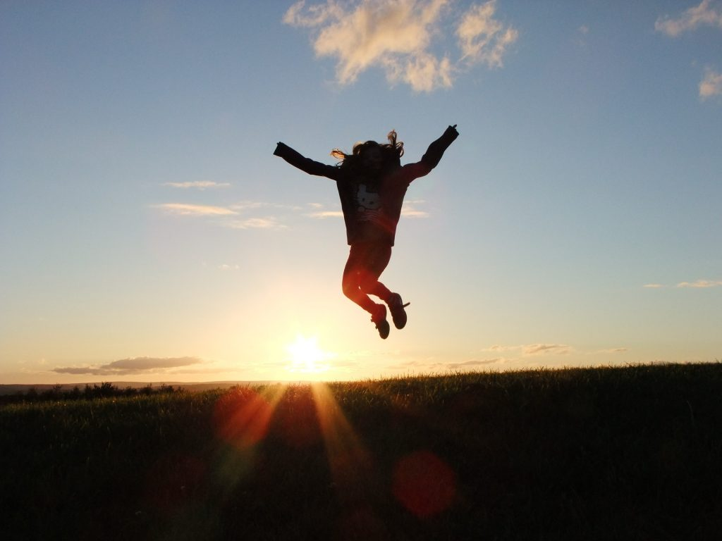 girl jumping in air against sunset